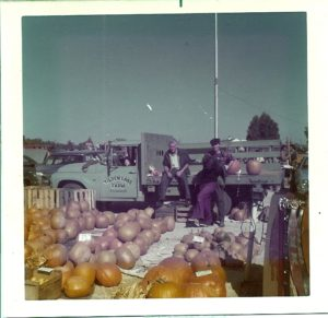 Herb, son John (in the truck cab), son Bruce, and camera-shy Barbara, selling leftover fall vegetables at the 110 Drive-In Flea Market, 1974.