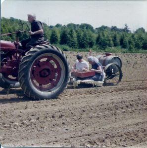 Herb driving the tractor with his wife Mable and son Lee on the setter, planting tree seedlings, 1977.