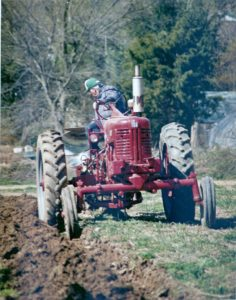 Herb plowing a field with the Farmall tractor in the early 1980s.