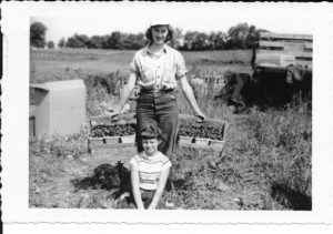 Farm work was shared by the whole family. Herb's wife Mable is shown here in the early 1950s with her niece Judy Potters, bringing in twelve quarts of fresh strawberries from the field.