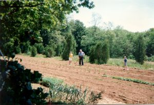 Herbert hoeing a field with his granddaughters Emily and Rebecca.