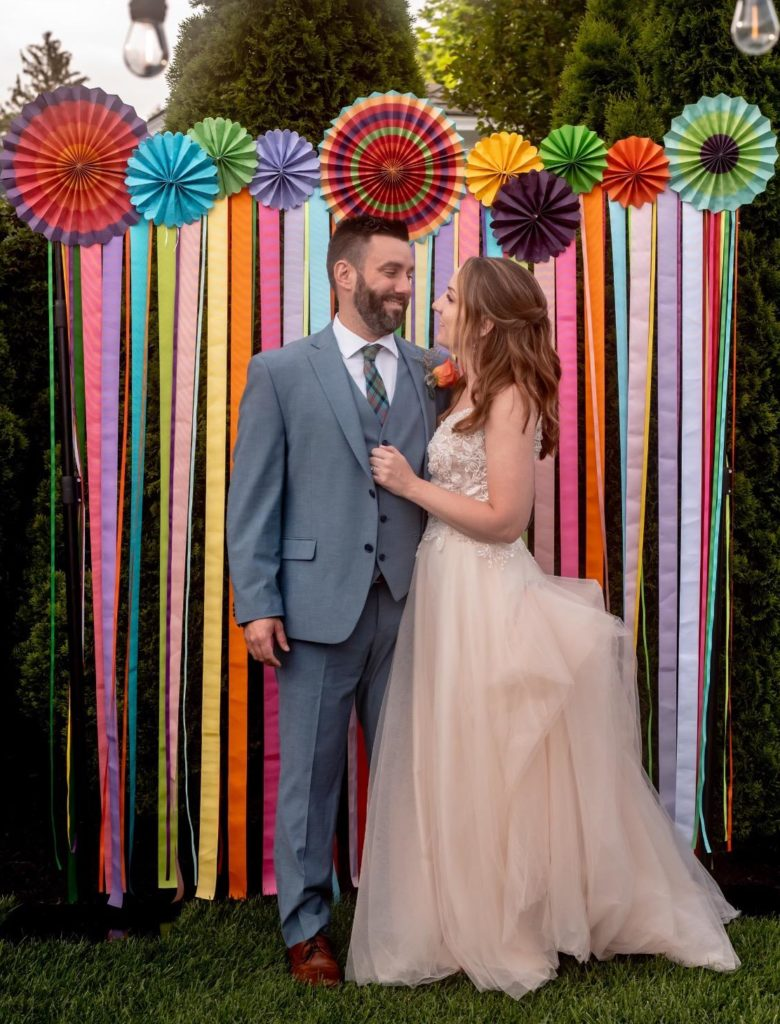Andrew and Katie stand together at their wedding before a multicolored backdrop. Andrew is in a grey suit and Katie is in a blush wedding gown. They are looking at each other and smiling.